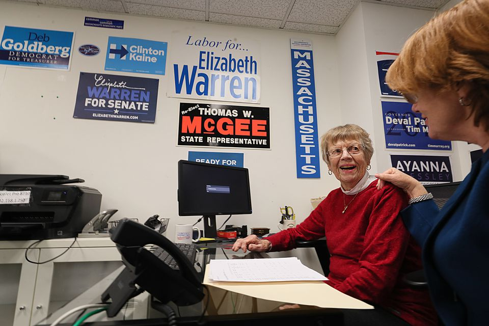 Jean Moulton (left), on her last day at the Massachusetts Democratic Party offices, gave papers and instructions to Jeannie Doherty, director of operations.