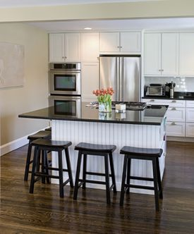 <b>GATHER ROUND</b>: Knocking down a kitchen wall and installing an island creates a more accessible, modern space.