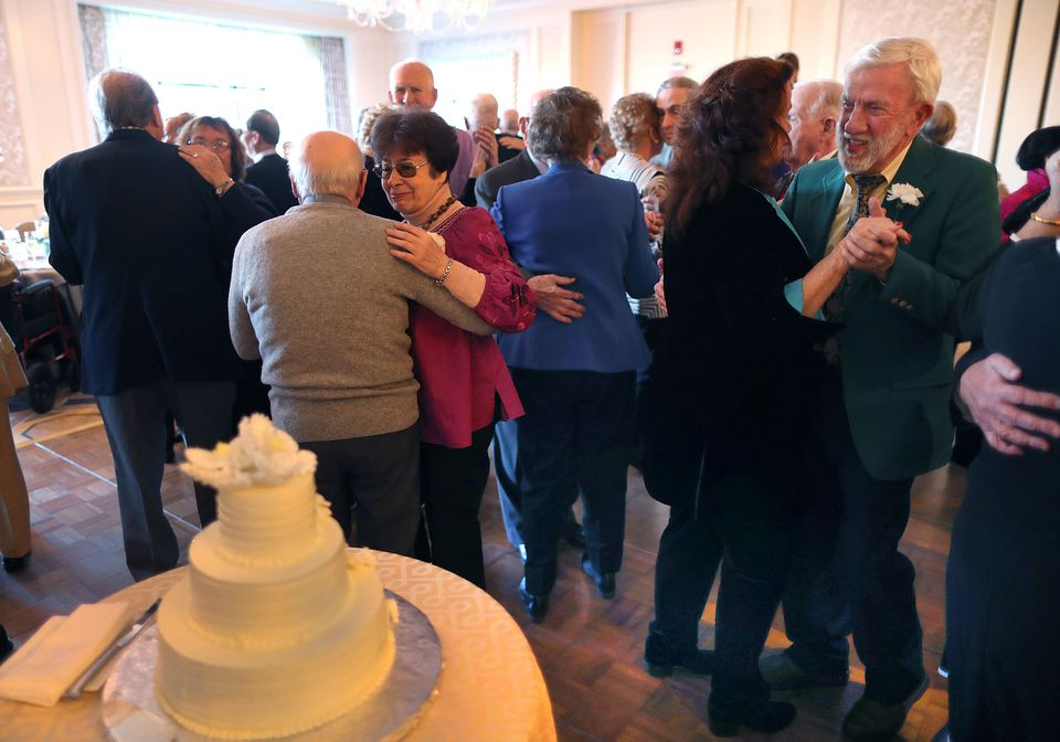 Couple danced near the anniversary cake at the annual Golden Wedding Anniversary Celebration.
