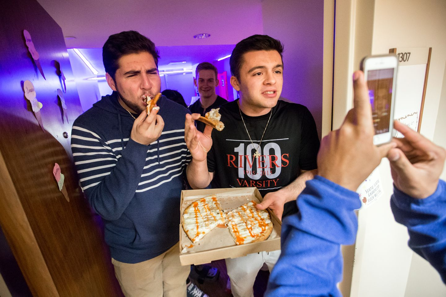 Students Eric Harpootian and Theodore Bakas received a pizza delivery from Marc Prophet of Stoovy Snacks, while Prophet live streamed the delivery to the company's followers on social media. Stoovy Snacks delivers food directly to students' rooms at Boston University's Student Village 2 dormitory.