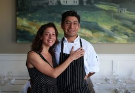 THE FARMHOUSE: Dora Tavel-Sanchez Luz and her husband, Gabriel Sanchez Luz, in their Needham restaurant, which opened in March, fueled by a Kickstarter campaign that helped them buy the rustic door and chairs for the place.