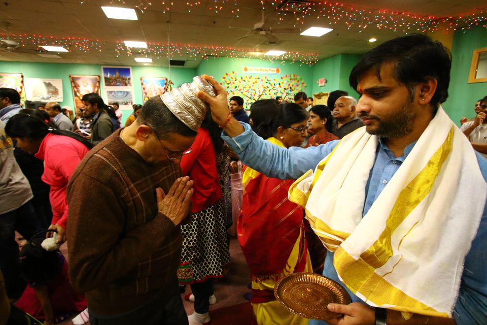 The temple's priest, Satish Sharma, blessed one of the devotees with a shatagopam.