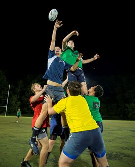 Members of the Mystic River U19 rugby club practice a line-out. Austin Mackay (left) and Shane O'Sullivan (right) are lifted by teammates to vie for the ball.