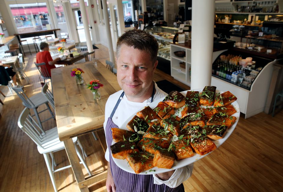 Ben Elliott, owner of Saltbox Kitchen and Saltbox Farm in Concord, shows off a platter of roasted salmon with maple ancho chili glaze.