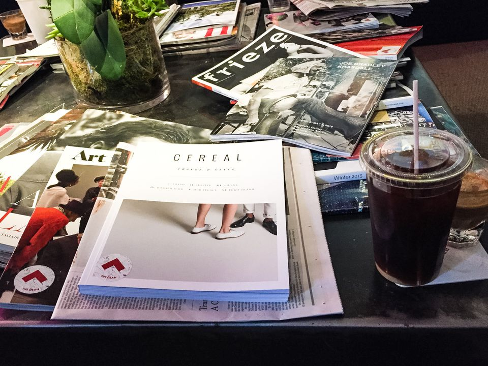 Coffee, art journals, and niche digests on a center table in Bolt.