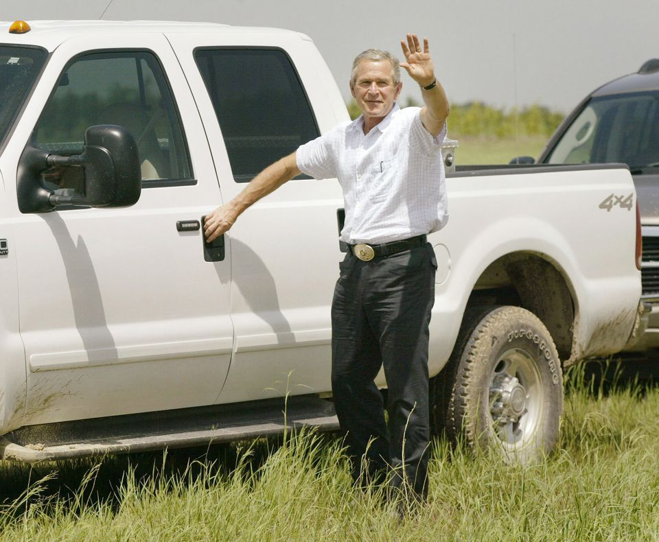 Then-President George W. Bush waved as he prepares to drive his pickup truck away after speaking to the press on his ranch in Crawford, Texas.