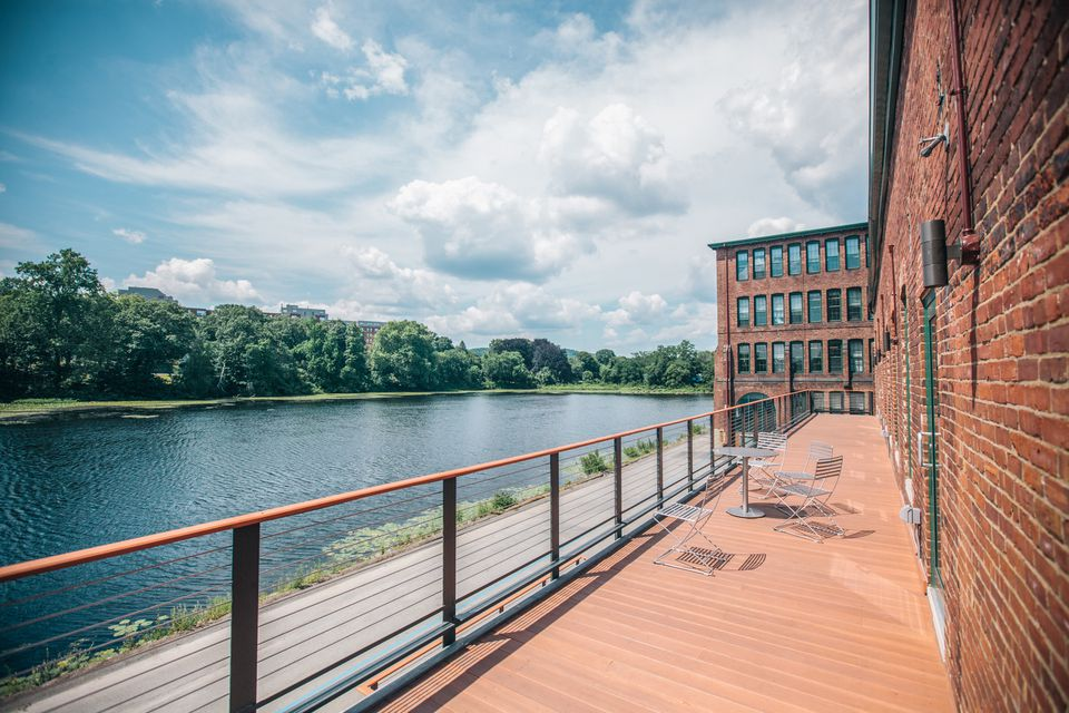 """Employees at CloudLock, a cloud security company based in the Watch Factory building in Waltham, enjoy dedicated deck space on the river. Suburban towns are branding the area """"Charles River Mill District."""""""