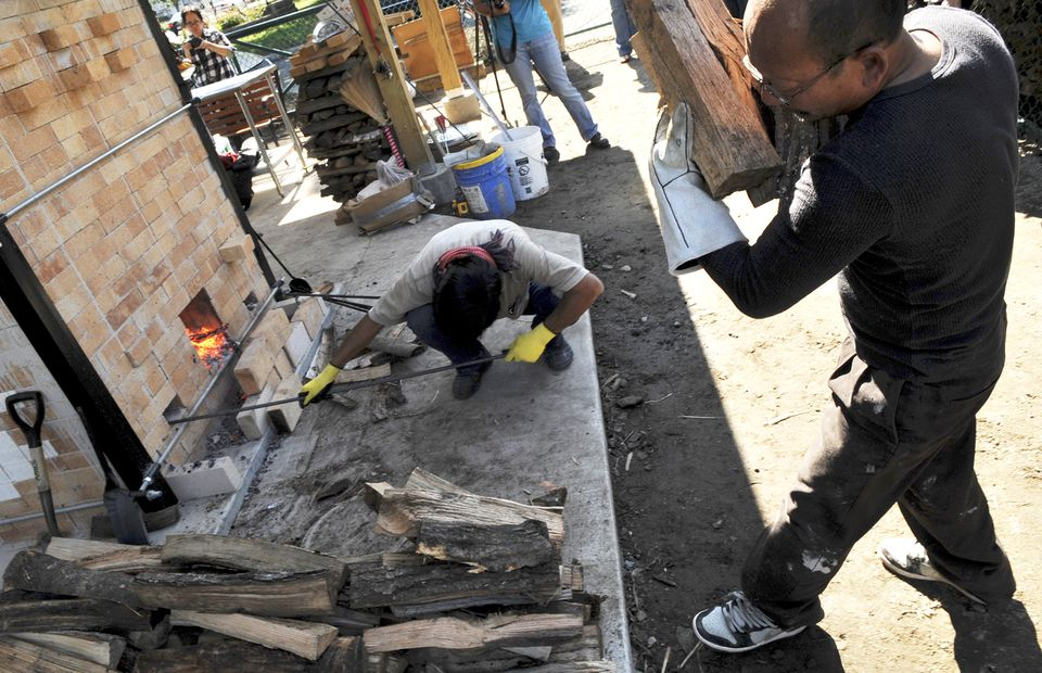 Yary Livan (right) brings wood for the new kiln. Kneeling, Kang Proeung, a fine arts teacher in Cambodia, helps start the kiln's first fire.