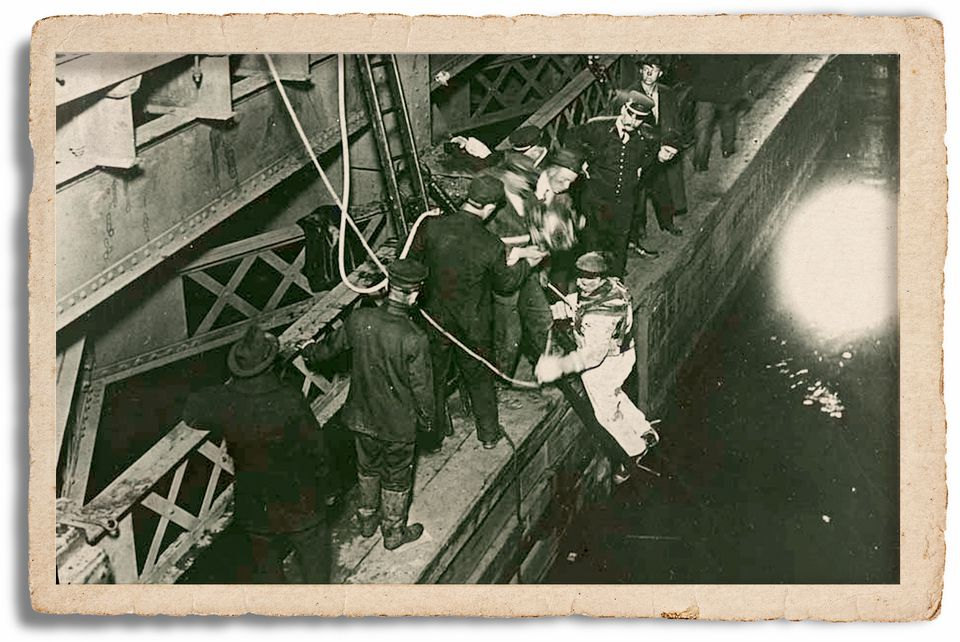 Peter Foley prepares to dive underneath the bridge on the night of the accident. Diving in those days was a matter of teamwork, with a heavy suit and helmet, weighted shoes, and lines connecting the diver to handlers on the surface. Foley was the first to discover that the streetcar was lying in the muck right side up, and he saw the bodies of many victims protruding from broken windows.