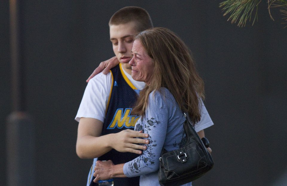 Shooting witness Jacob Stevens, 18, hugged his mother Tammi Stevens after being interview by police outside a high school where witnesses were brought for questioning in Aurora, Colo.