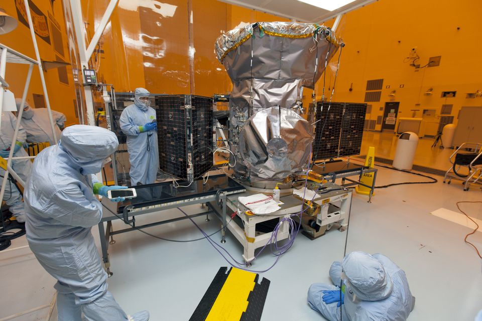 Technicians dressed in clean room suits worked on TESS with its solar panels deployed at the Kennedy Space Center in Florida in February 2018.