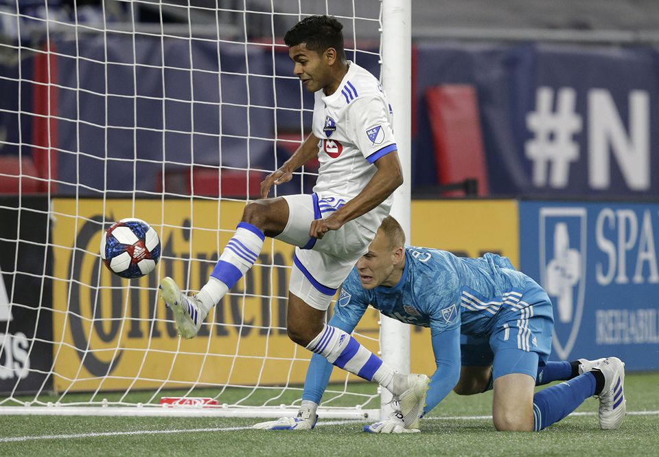 Montreal's Shamit Shome scores against New England goalkeeper Cody Cropper Wednesday.