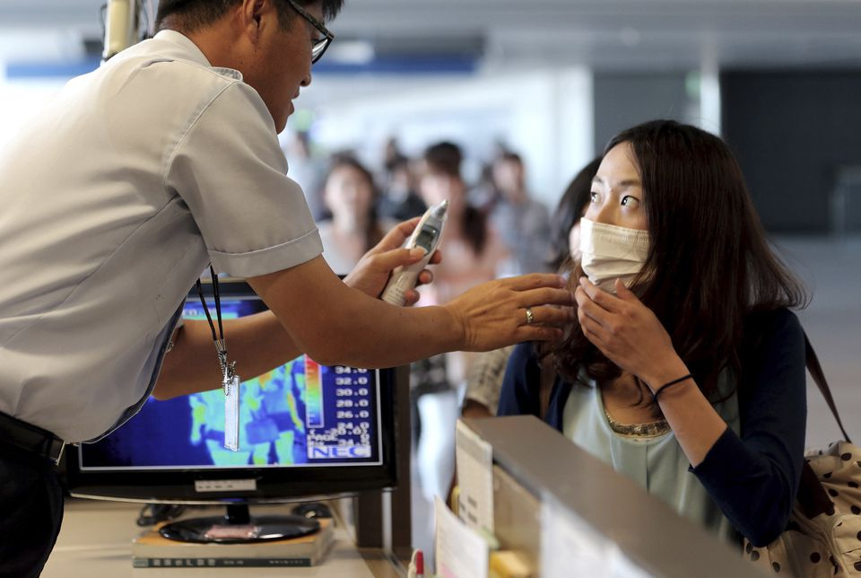 A quarantine officer checked the body temperature of a passenger at Incheon International Airport in South Korea.