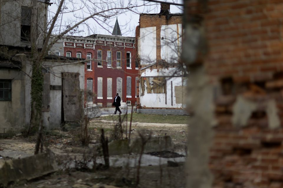 A man walked past boarded-up houses and vacant lots in Baltimore. One-third of Baltimore households live on less than $25,000 each year.