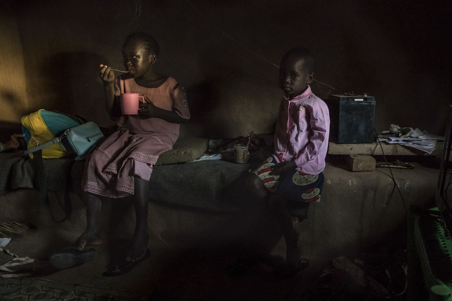 Lynda (left) and Julie (right), daughters of Achayo Loum, sat in the family's home in the UNHCR refugee camp.
