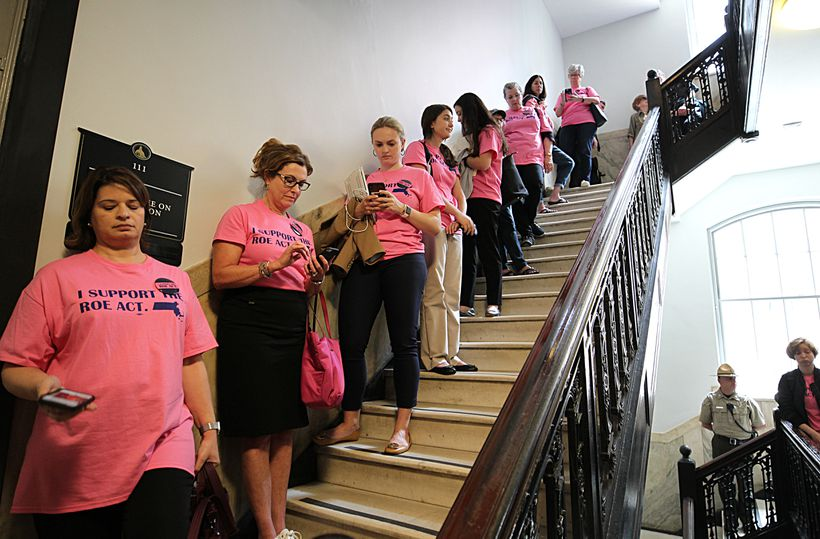Pro-choice supporters of the the Roe Act lined a staircase waiting to attend a hearing.