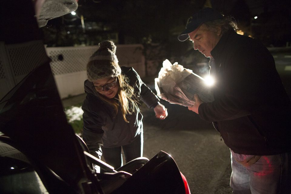 Globe photographers Jessica Rinaldi, left, and Bill Greene worked in the pre-dawn hours to deliver newspapers in Cambridge.