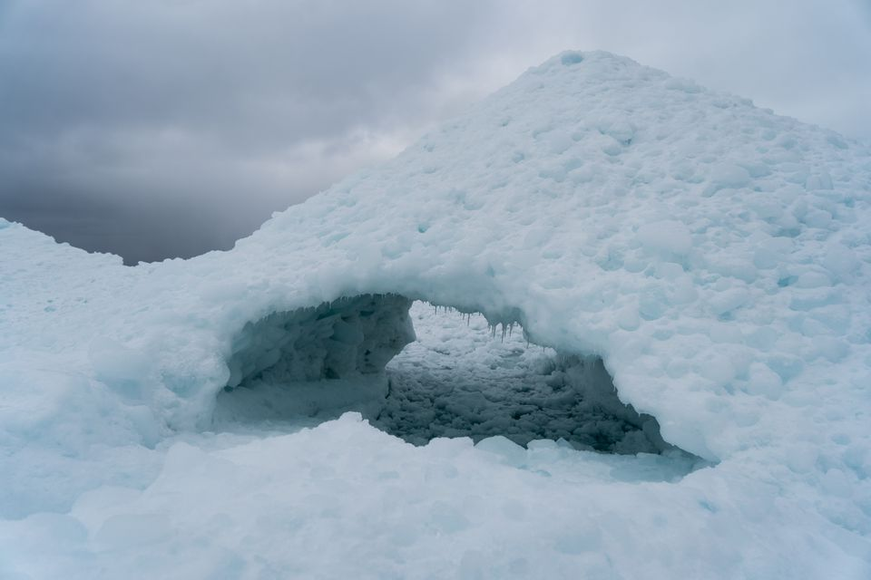 An ice bridge, an early step in the formation of a natural ice cave, on the shores of Lake Superior in Ontario. Like any phenomenon dependent on ice, cold, and weather patterns, Ontario's renowned ice caves are under threat from climate change; observers predict the lake could be ice-free within decades.