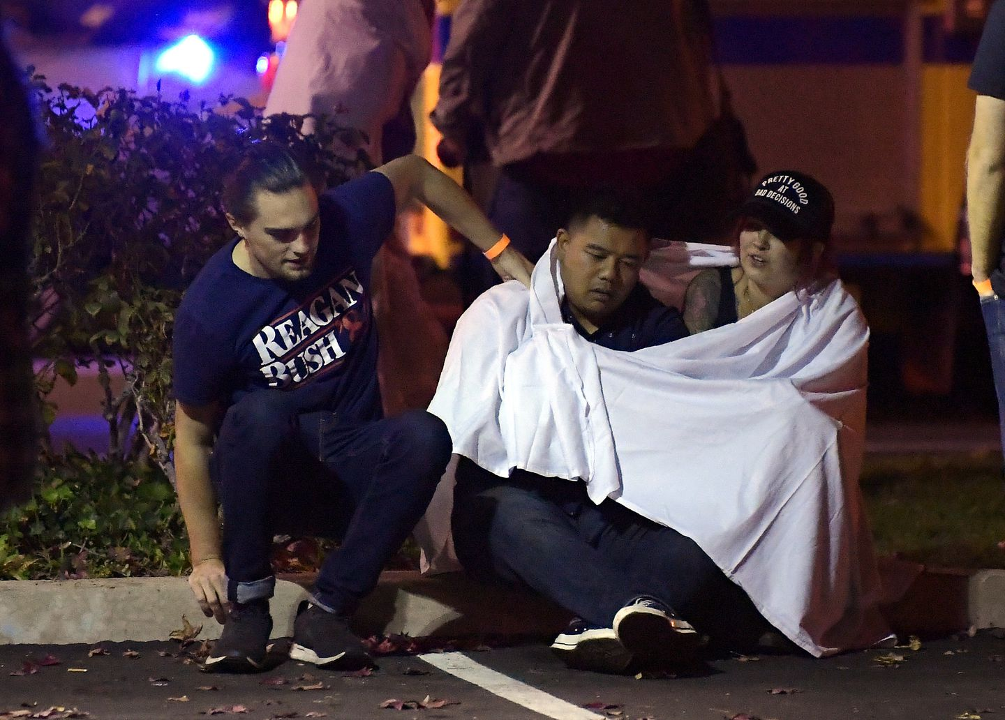 People comforted each other as they sat near the scene.