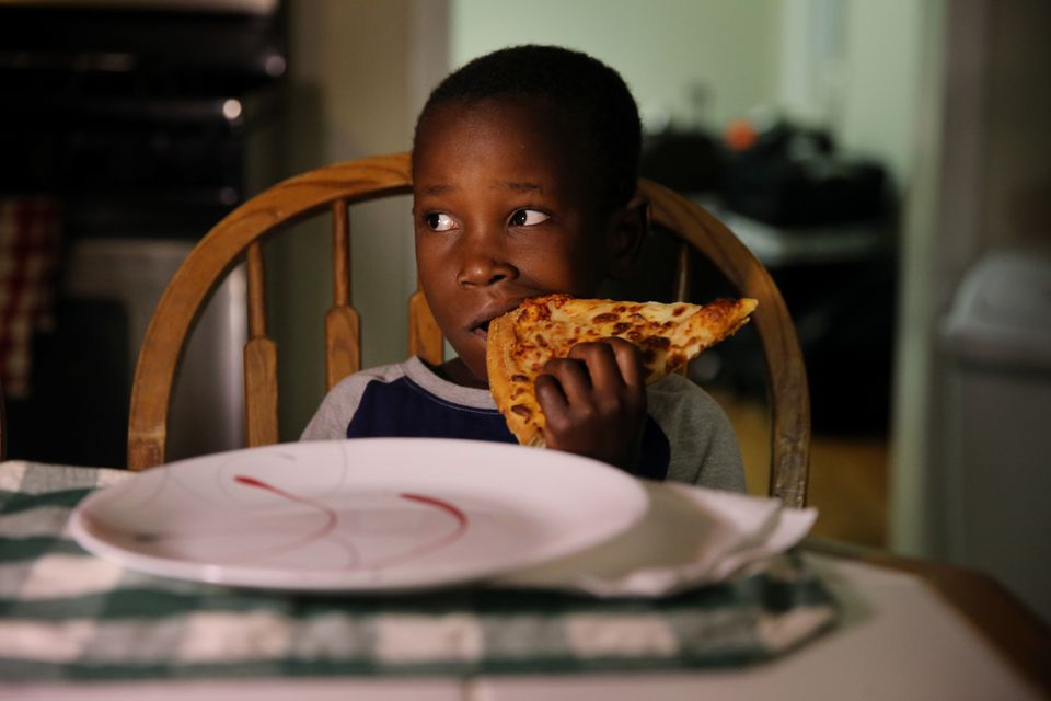 Sarah, 7, tried a slice of pizza at the family's new home in Lowell.