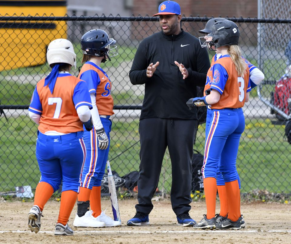Newton South coach Jesus Rodriguez speaks to (from left) Adalia Rodriguez (7) Halley Thayer and Stephanie Little.