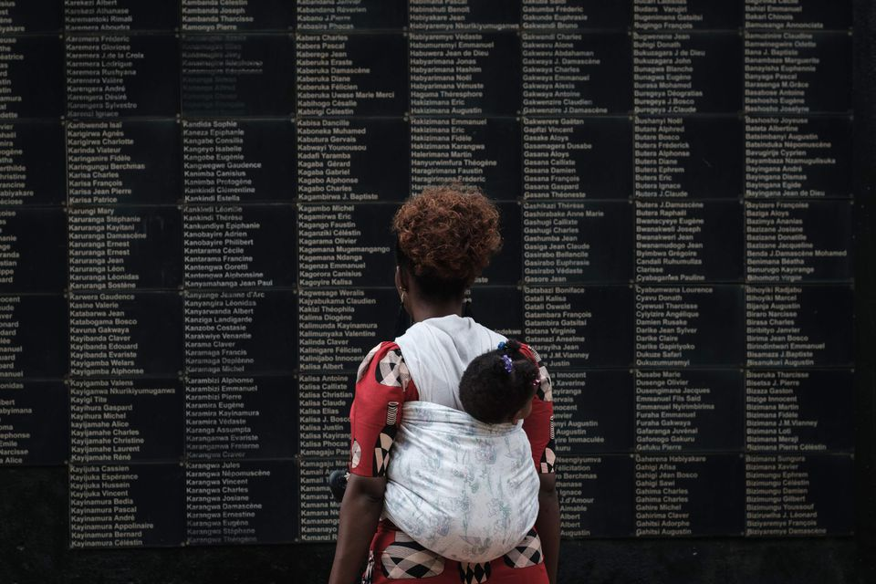A woman carrying her child looked at the wall of victims' names as Rwanda marked the 25th Commemoration of the 1994 Genocide at the Kigali Genocide Memorial in Kigali, Rwanda.