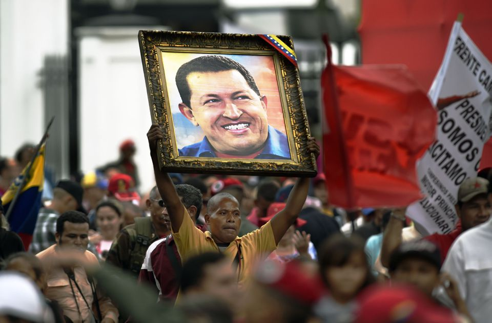 A supporter of Venezuelan President Nicolas Maduro holds a portrait of late Venezuelan president Hugo Chávez during a demonstration march in Caracas on April 7, 2016.