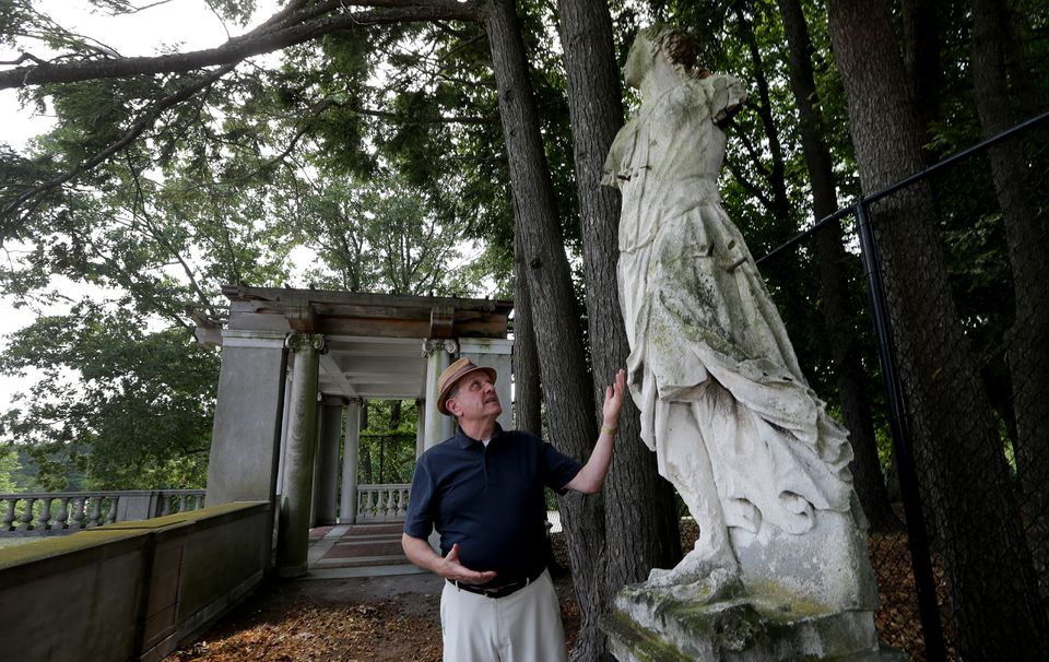 Skip Moskey, author of a new biography about Larz and Isabel Anderson, looks up at an original statue that still stands on the Brookline estate.,