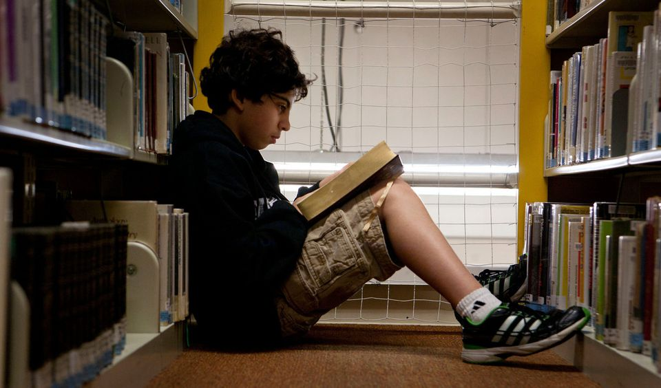 Samuel Daitsman, 13,  finds reading room between the shelves at the overcrowded Millis Public Library.