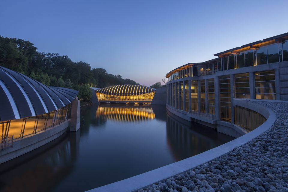 Crystal Bridges Museum with its arch-roofed pavilions that appear to float above the water.