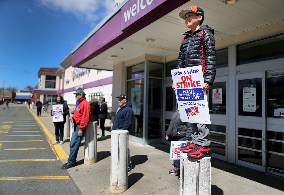 Nathan Ely, 11, stood on a column outside a Stop & Shop store in Watertown. His father, Christian Ely, is the produce manager there and has worked at Stop & Shop for 32 years. Ely is on school vacation this week.