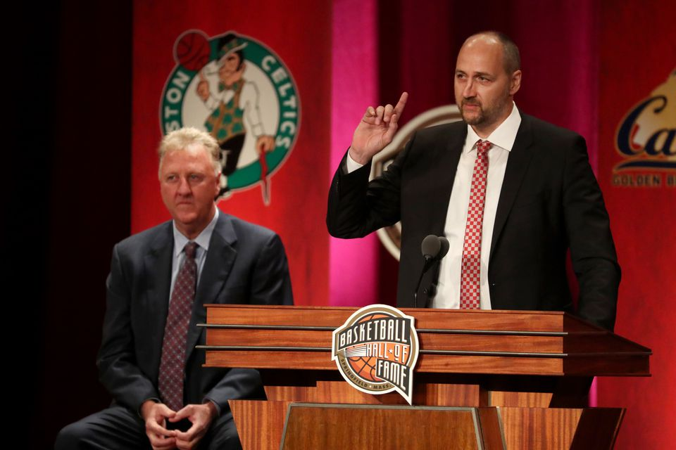 Presenter Larry Bird watches as fellow former Celtic Dino Radja gives his Hall of Fame induction speech.