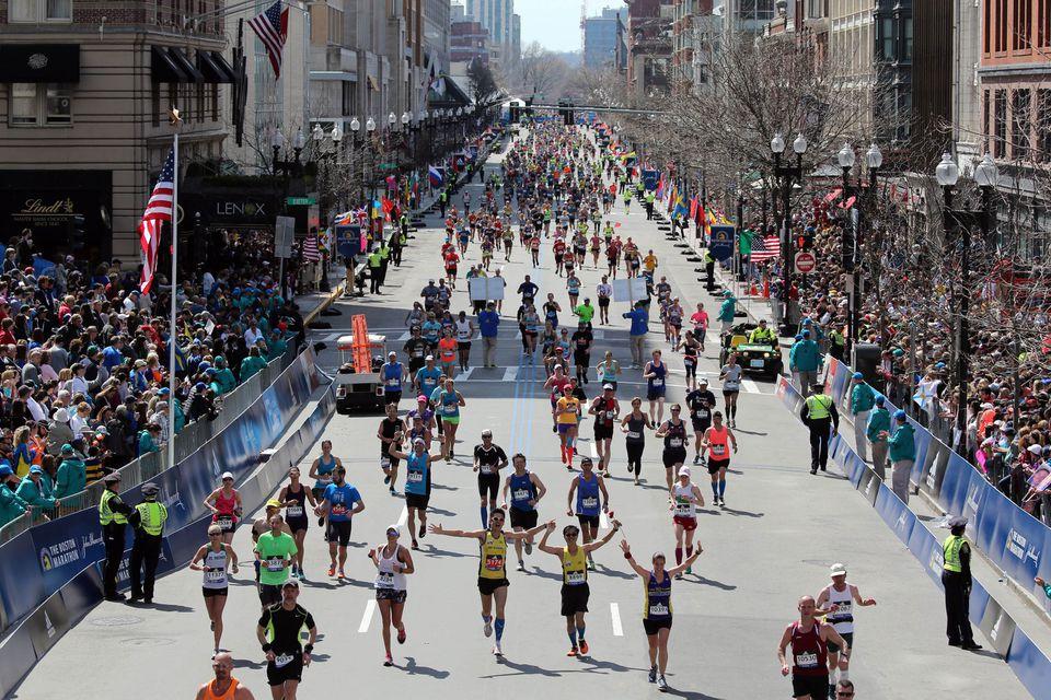 Runners stream down Boylston Street to the Boston Marathon finish line.