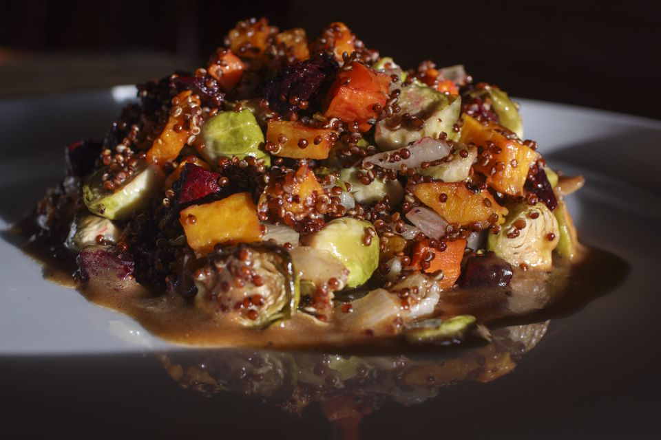 A vegetable salad of carrots, baby Brussels sprouts, and roasted onion, punctuated with chunks of beets and mixed with red quinoa grain.