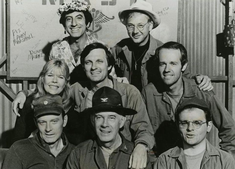 """Mr. Christopher (top right, alongside Jamie Farr) played a soft-spoken chaplain on """"M*A*S*H.'' Other cast members included (clockwise from left) Loretta Swit, Alan Alda, Mike Farrell, Gary Burghoff, Harry Morgan, and Larry Linville."""