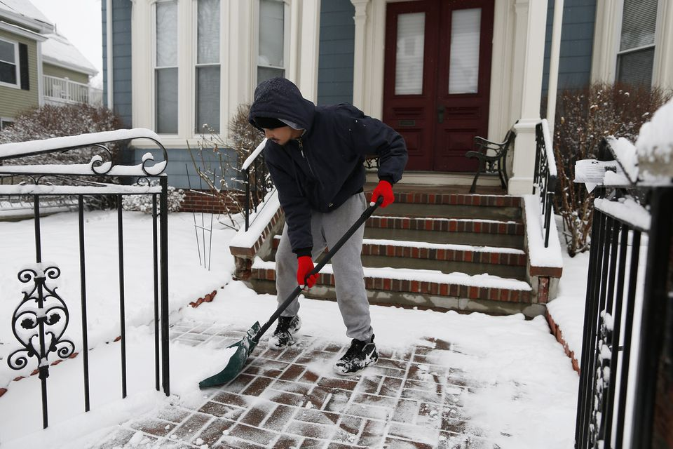 Jose Rodriguez of Lynn shoveled snow in Somerville on Monday.