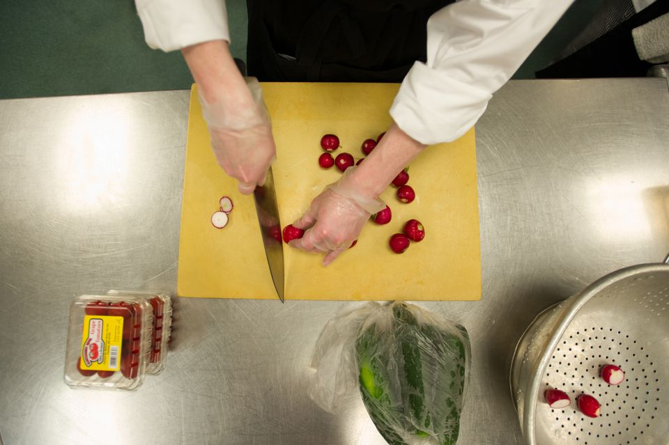 Michelle Lord cut radishes while participating in the Community Kitchen training program at the Rhode Island Community Food Bank in Providence.