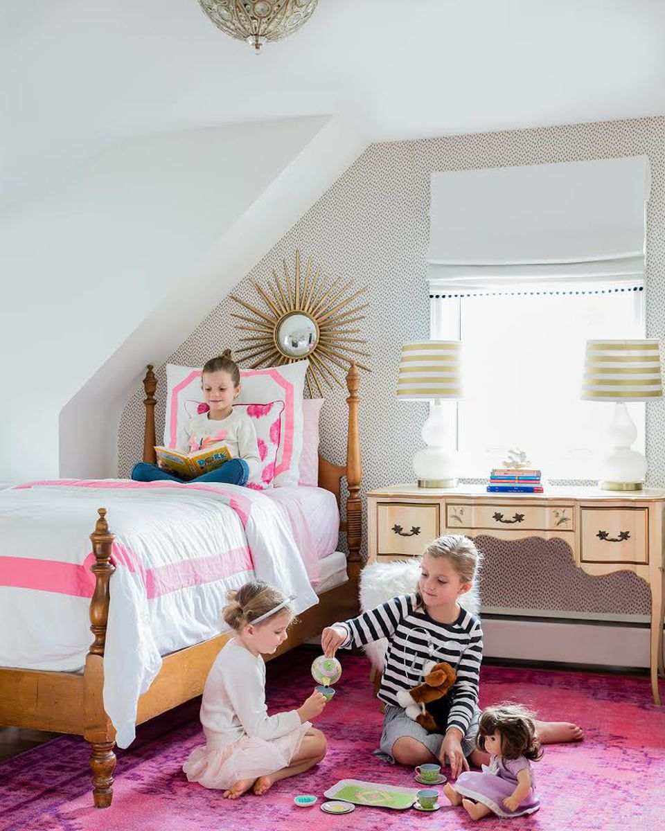 Designer Dina Holland scored the wallpaper at a yard sale. A Martha Stewart Home mirror and a fluffy pink stool add pizazz. The lamp on the antique desk is from Target.