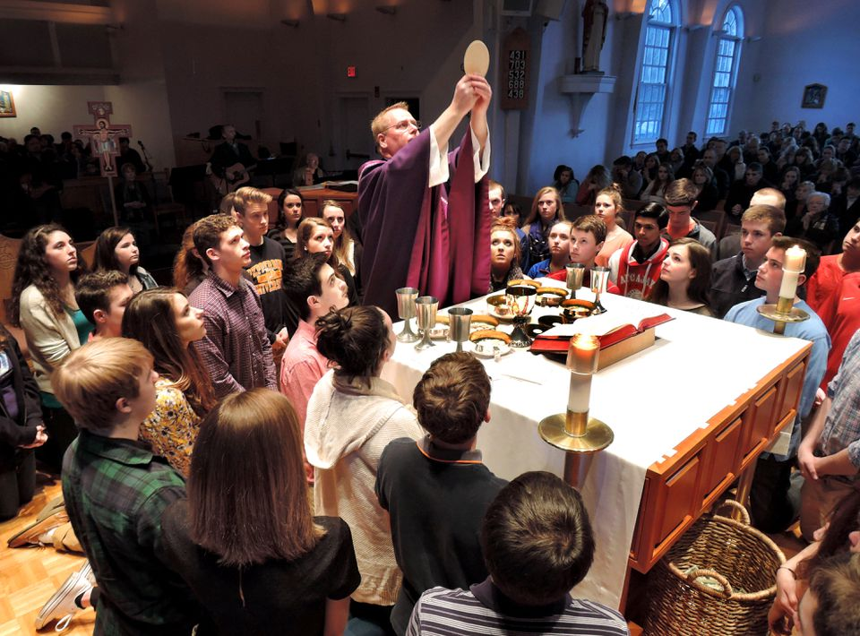 At the Life Teen Mass at St. Mary of the Sacred Heart Church in Hanover, youths gathered around the Rev. Chris Hickeyon the altar for the consecration of the eucharist.