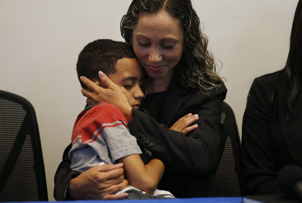 An Immigrant mother who asked to be identified by the initials W.R. cradled her 9-year-old son, A.R., during a press conference at the Brazilian Worker Center in Boston.