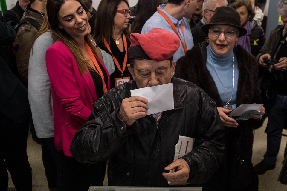 A voter wearing a traditional Catalan hat known as a barretina kissed his ballot before casting it on Thursday in Barcelona. Voters elected a new regional government.