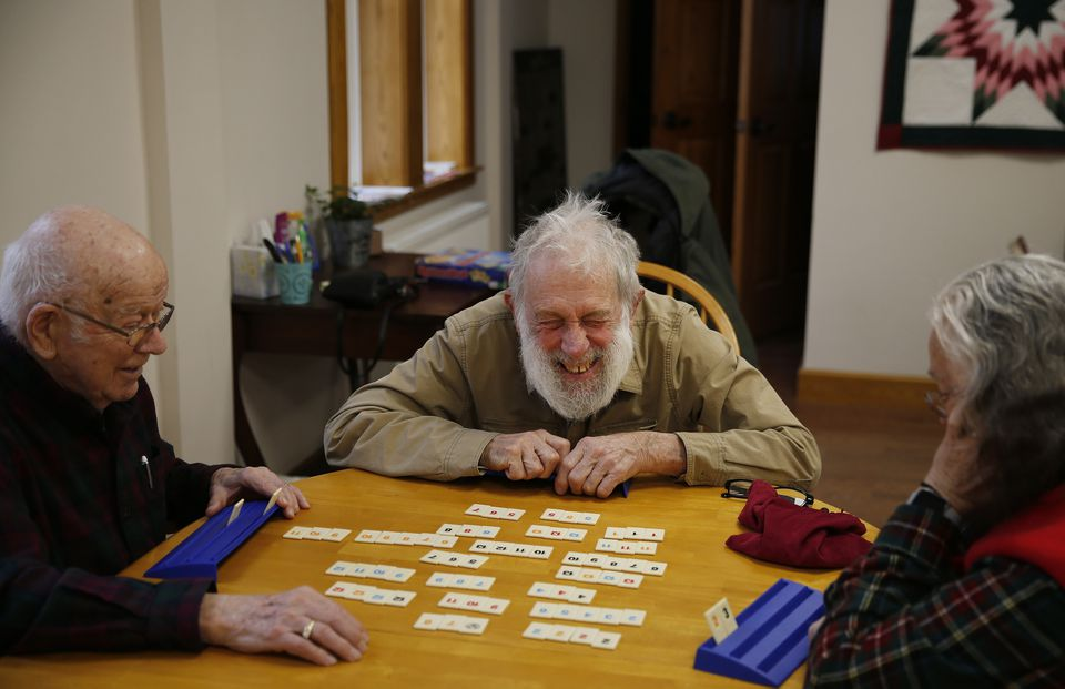 David Migneault, of Garland (center) laughed as he plays Rummikub with his wife, Peggy, (right) and friend Alden Bent, of Dover-Foxcroft downstairs in Central Hall in Dover-Foxcroft, Maine.
