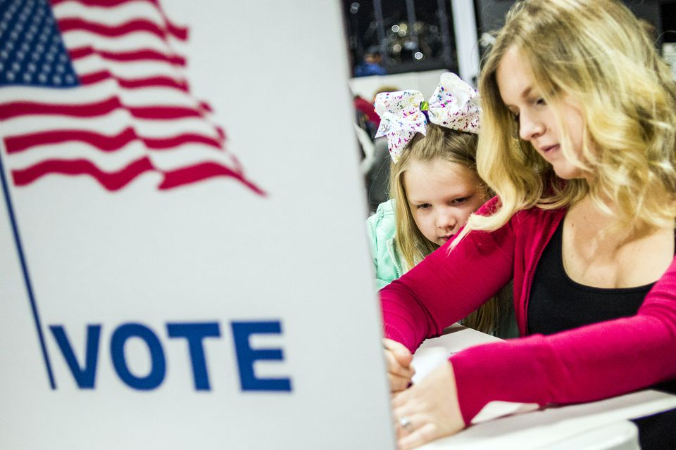Haidyn Jozwiak, 7, leans on her mother Kassi Jozwiak's shoulder, as she watches her vote on Tuesday at New Testament Community Church in Burton, Michigan.