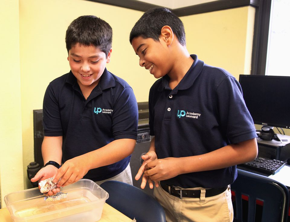 At UP Academy Leonard Middle School in Lawrence, Jacob Hernandez (left) and De'Andre Lebron worked on a science experiment using boats filled with pennies.