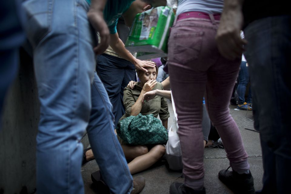 Irama Carrero was aided by fellow shoppers after fainting in a food line outside a grocery store in Caracas earlier this year.