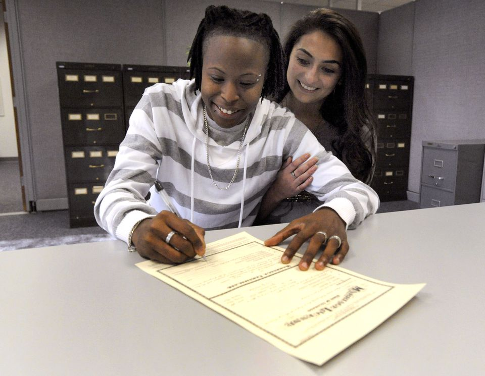 Ebony Brown (left) signed her marriage license with Danielle Brown, making them the first gay couple in Weld County, Colo., to be married at the clerk and recorders office.