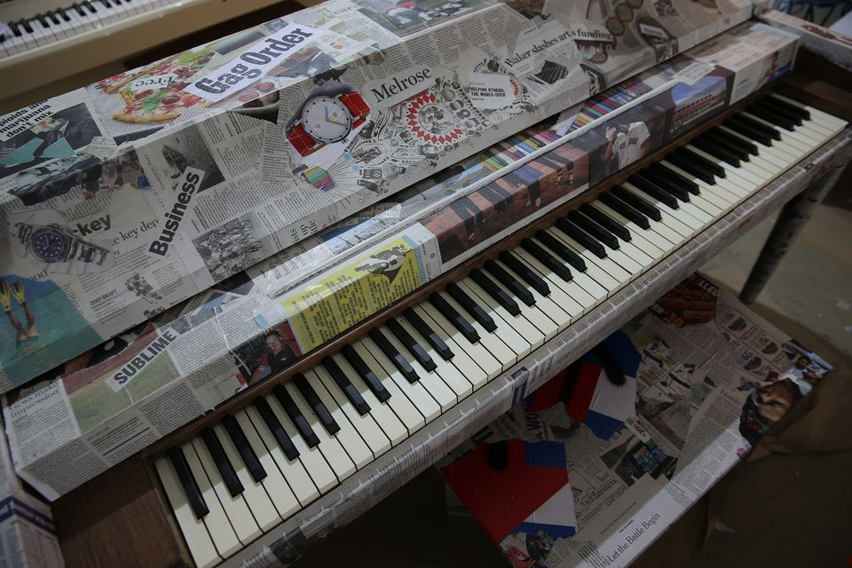 Pages and scraps from The Boston Globe were used to cover one of the pianos.