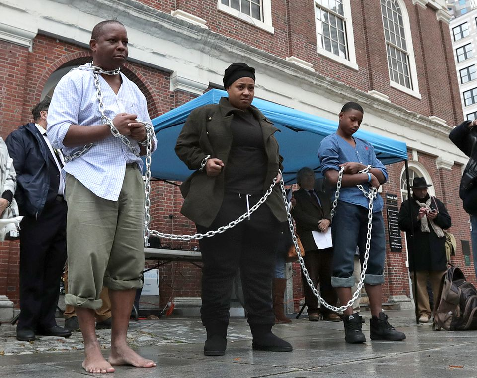 Kevin Peterson (left), Celestina Crenshaw, and Avonte Dabney portrayed slaves during's Saturday's reenactment at Faneuil Hall.