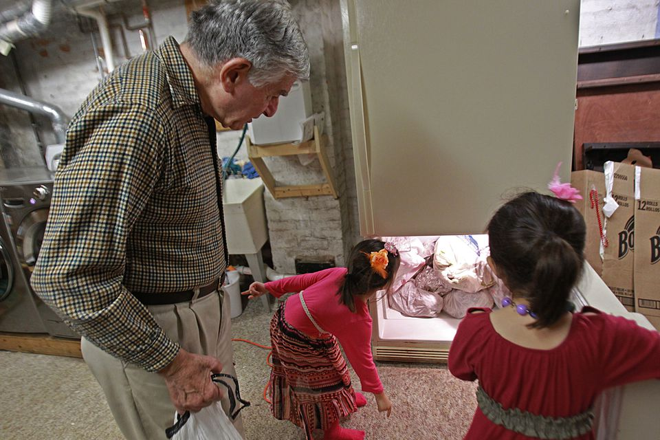 Former Governor Michael Dukakis helped his neighbors, Lilac and Isabella Nguyen, five year old twins, get the donated turkey carcasses into his neighbor's freezer.
