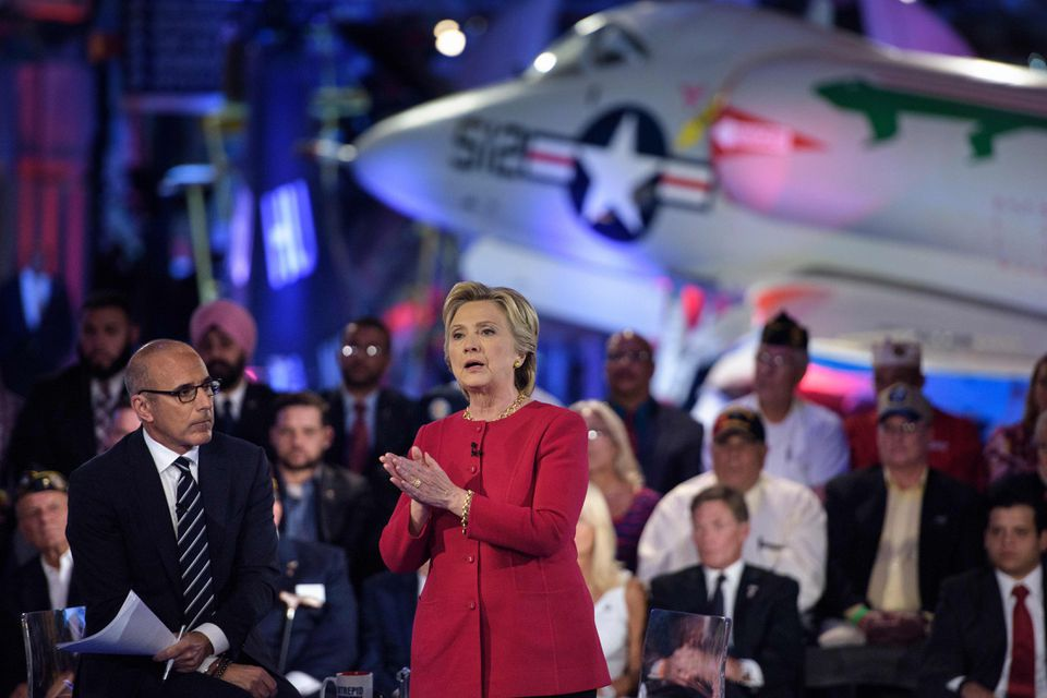 """Matt Lauer (left), co-host of """"The Today Show,"""" listened as Hillary Clinton speaks spoke during a forum Wednesday night."""